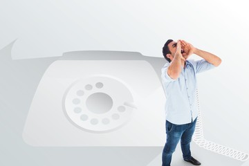Shouting casual man standing against retro telephone