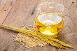 Rice bran oil in bottle glass and unmilled rice on wooden backgr - 69580933