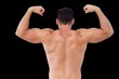 Rear view of shirtless muscular man flexing muscles