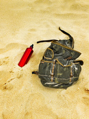 Backpack and canteen water bottle in the sand of a beach.