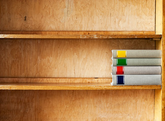 four new books on a wooden shelf