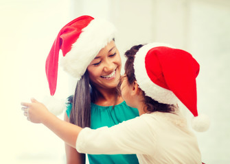hugging mother and daughter in santa helper hats