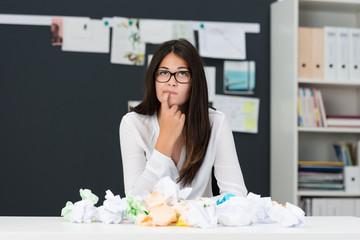 junge frau sitzt nachdenklich vor zerknülltem papier