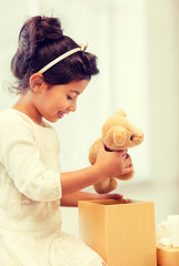 happy child girl with gift box and teddy bear