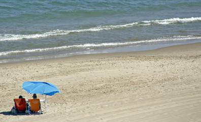 pareja en la playa con sombrilla