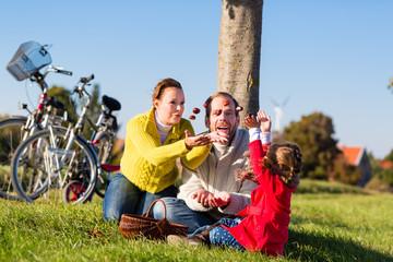 Familie sammelt Kastanien im Herbst