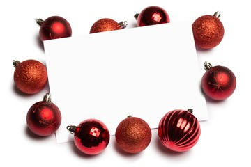 Red christmas baubles surrounding white page