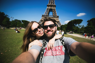 Romantic couple making selfie in front of Eiffel Tower while