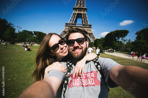 Romantic couple making selfie in front of Eiffel Tower while - 69584180