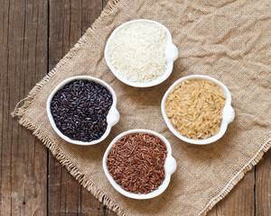 Variety of rice in bowls on wooden table