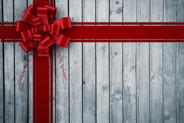 Composite image of red christmas bow and ribbon