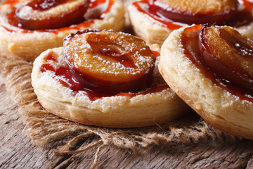 Pies of flaky pastry with plums close up horizontal