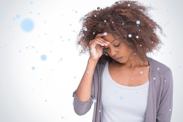 Composite image of sad woman holding her forehead with her hand