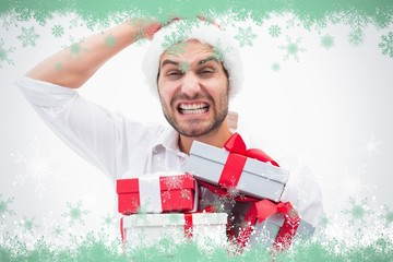 Composite image of stressed festive man holding gifts