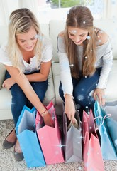 A smiling pair of girls looking at the shopping