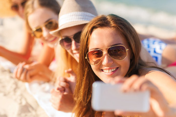 close up of smiling women with smartphone on beach