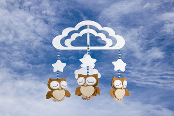 Three Felt Owls on Baby Cot Mobile Against Cloudy Sky
