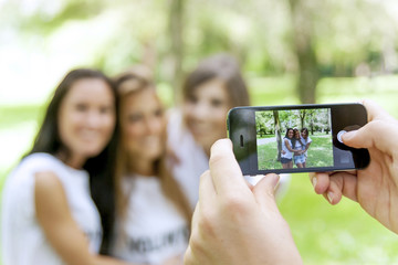 group of teenagers takes pictures with a smartphone