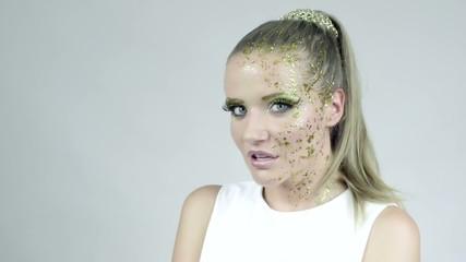 Model in golden make-up posing in studio. Fashion.