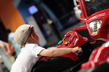 Kid playing arcade simulator machine