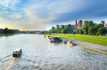 Tourist boats on Vistula river with Wawel Royal Castle, Poland