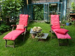 Zwei Liegestühle mit rosa Kissen in einem Garten in Löhne