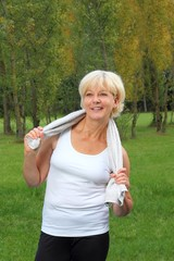 Dame beim Sport mit Handtuch laechelnd