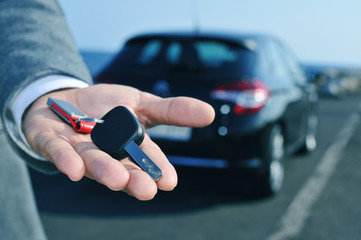 man offering a car key to the observer