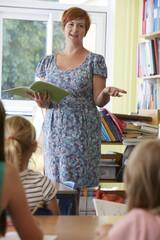 Elementary School Teacher With Pupils In Classroom