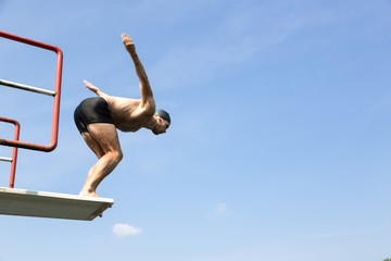 Man jumping off diving board at swimming pool