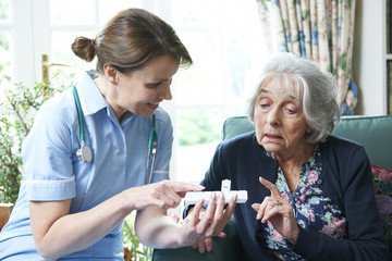 Nurse Advising Senior Woman On Medication At Home
