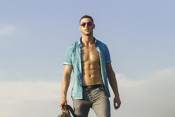 Trendy guy in sunglasses and a blue shirt against the sky