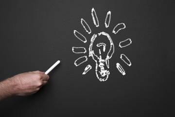 Drawing light bulb on the blackboard