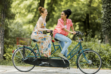 Young women riding on the tandem bicycle