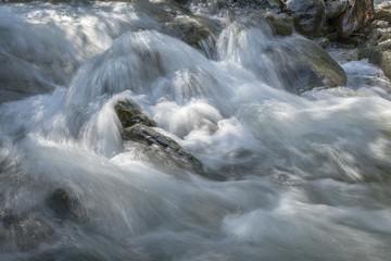 Raging torrent flowing between the rocks