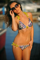 Sexy young woman in bikini posing at marina boat.