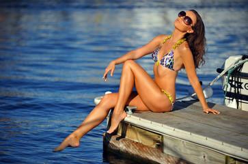 Attractive girl in bikini posing pretty on the pier.