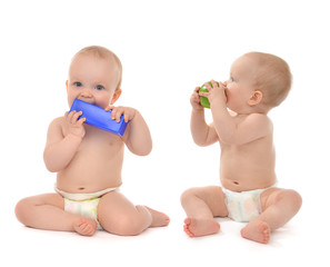 Two infant child baby toddlers sitting eating blue toy and green