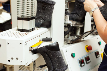 Worker adjusts machine for production of footwear