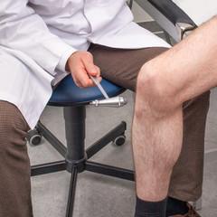 Arzt testet Reflexe beim Patienten mit Reflexhammer