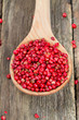 pink peppercorn in a spoon on wooden background