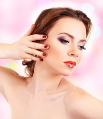 Beautiful young woman with bright make-up on light background