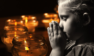 Praying child with candles on background.