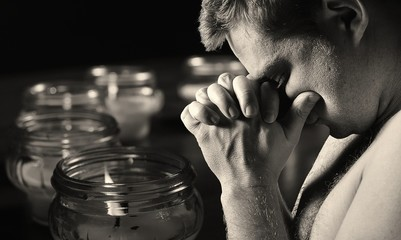 Praying man with candles on background.