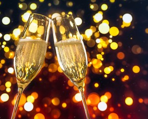 champagne flutes with golden bubbles on colorful bokeh