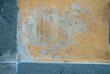Muro giallo con graffi, intonaco danneggiato