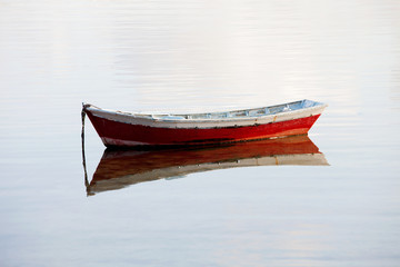 Lone red boat floating