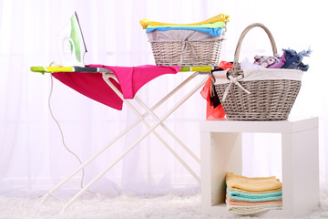 Baskets with laundry and ironing board