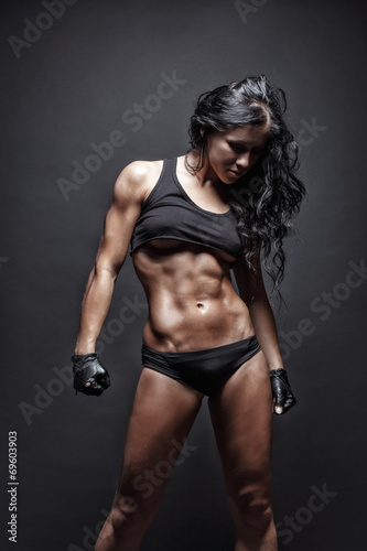 sexy young muscled fitness brunette girl posing over black