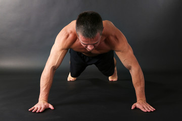 Handsome young muscular sportsman execute exercise
